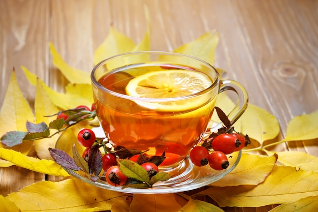 The table decorated with autumn leaves, berries and fresh tea