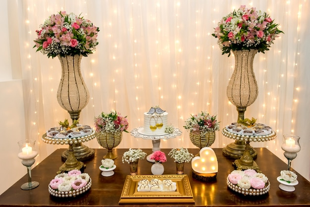 결혼식 파티에서 케이크, 사탕, 양초, 꽃, 장식품으로 장식된 테이블.