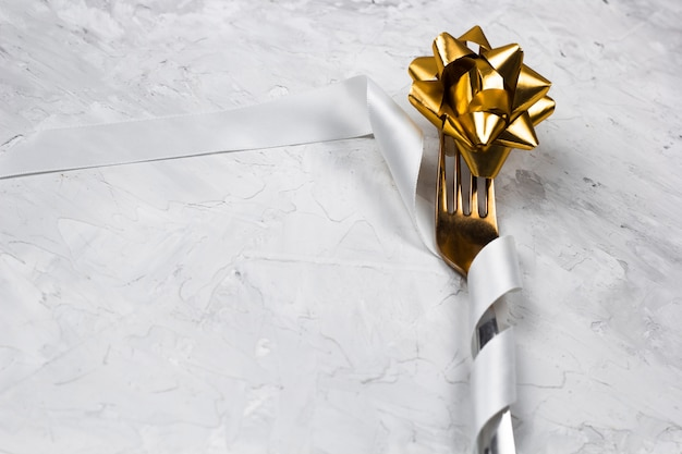 Table decoration for a dinner, golden fork with white shiny satin ribbon