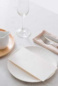テーブルデコレーション。白いプレート、フォーク、灰色の石のプレート上のナイフ