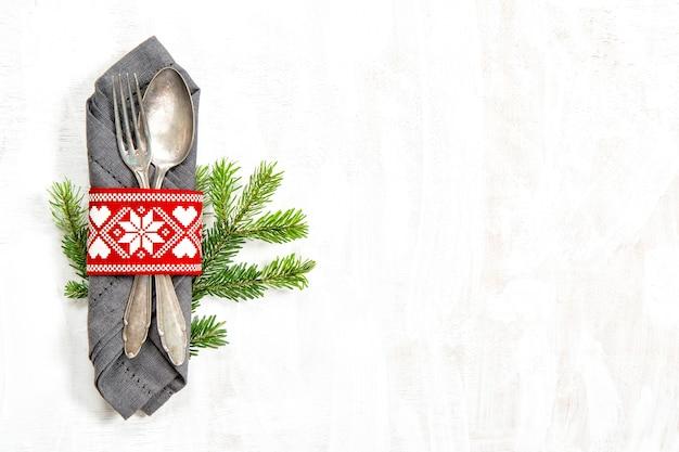 白い背景の上のクリスマスツリーブランチとテーブルの装飾