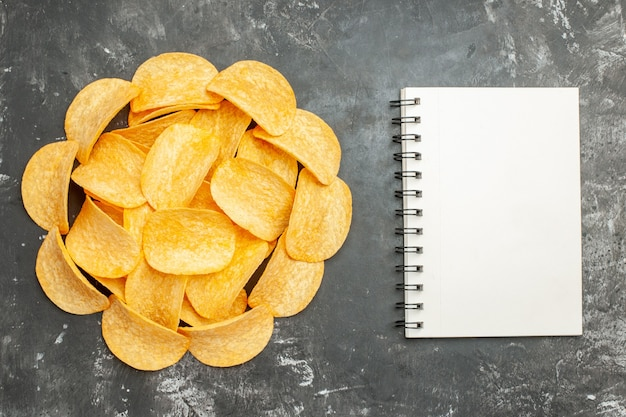 Table decoration with homemade potato chips on notebook on gray background