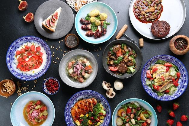 Вид сверху еды стола. набор посуды на столе. интернациональный набор блюд. вегетарианские и мясные и сырые.