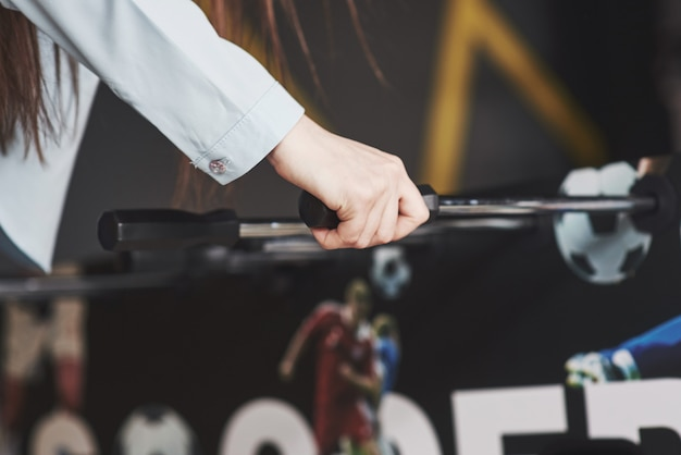 Настольный футбол в развлекательном центре. красивая девушка играет в футбол