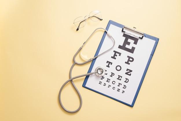 Таблица для проверки остроты зрения и медицинского стетоскопа на желтом фоне. понятие о глазной диагностике, выявлении глазных болезней в офтальмологии