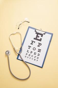 시력 검사 및 의료 청진기 테이블은 노란색 표면에 있습니다. 안과에서 눈 진단의 개념, 안과 질환의 발견