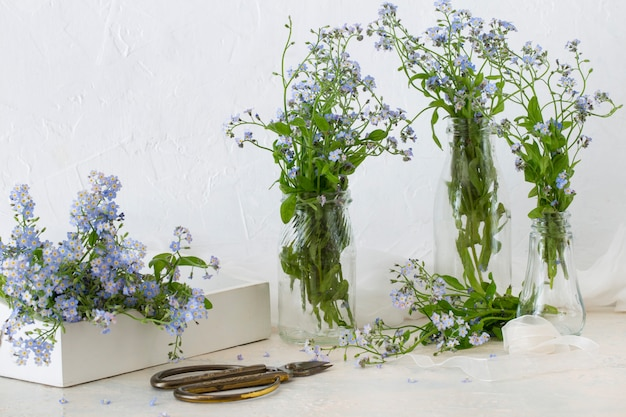 On the table, forget me not in glass vases, forget me nots in a box, scissors and ribbon