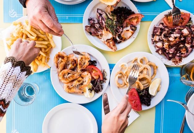 Стол, полный еды на обед - морская рыба и здоровая пища - сверху и сверху - некоторые руки берут еду из середины стола