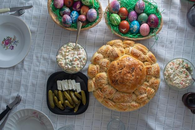 Стол полный еды на пасхальный праздник. цветные яйца и хлеб стреляют из верхнего угла