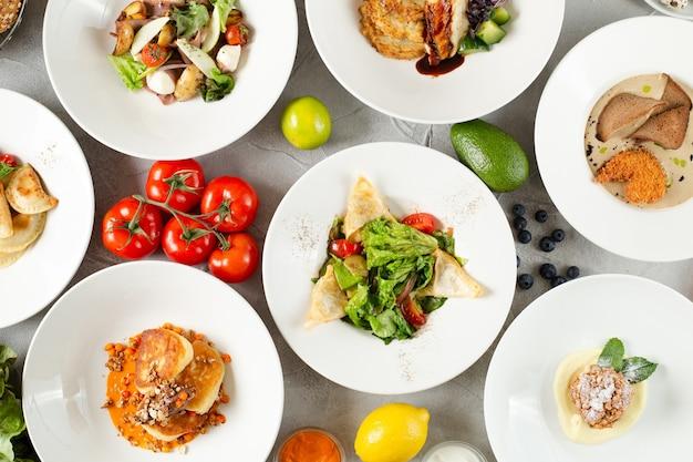 콘크리트 테이블에 음식이 가득한 테이블. 테이블에 접시 세트입니다. 테이블 상단 보기에 고기 샐러드와 디저트입니다.