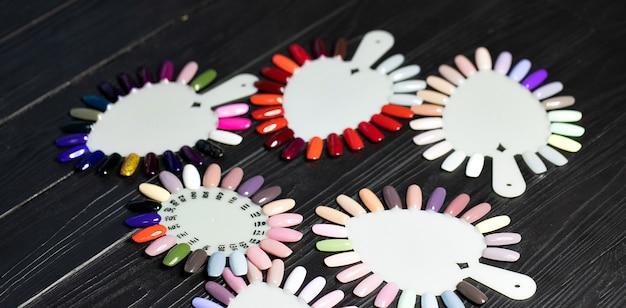 Стол полон посуды для маникюра, маникюрных инструментов, лаков для цветов на палитре. аксессуары для дизайна ногтей.