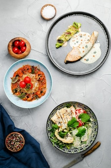 해산물이 가득한 테이블. 연어 스테이크 구운 새우와 아보카도 상위 뷰가 있는 오징어 샐러드, 해산물 테이블 개념