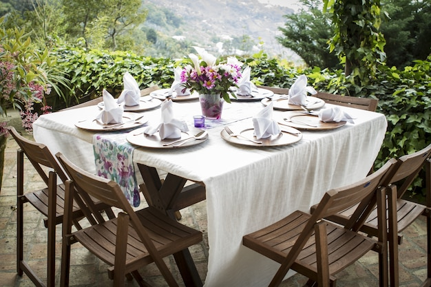 Table full of plates and a flower vase on a beautiful balcony with an amazing view
