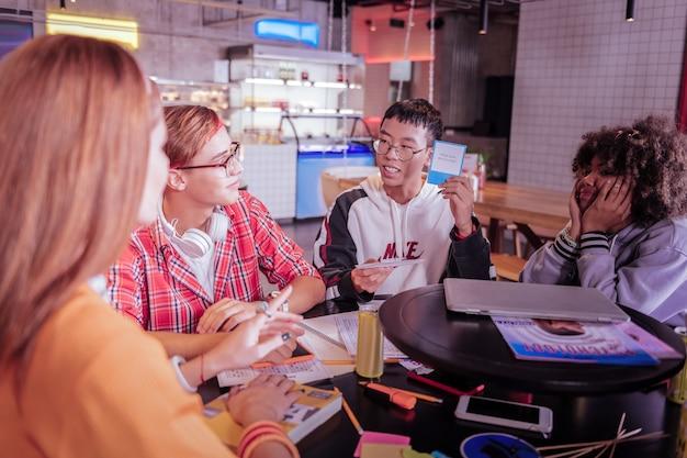 Настольная игра. красивая брюнетка с улыбкой на лице во время разговора с друзьями
