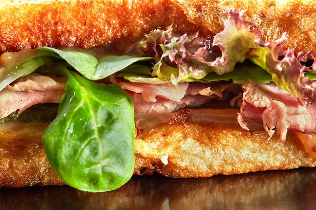 ハム、サラダ、キュウリ、グリルトーストのサンドイッチのスタックのテーブル画像