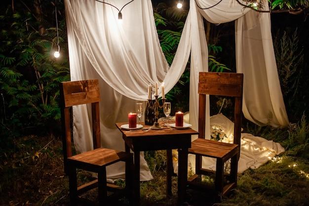 Столик в лесу, романтический ужин на двоих при свечах. белые шторы на дереве, гирлянда из