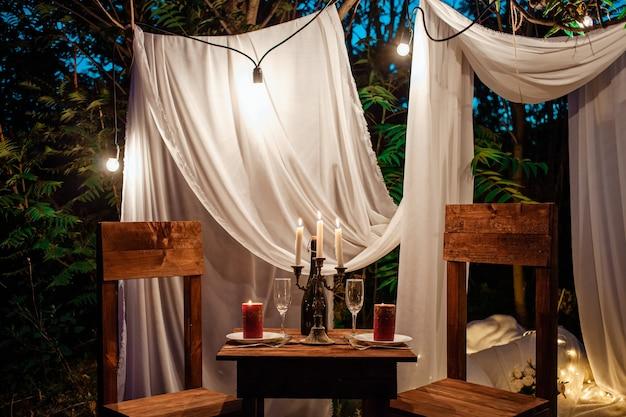 Столик в лесу, романтический ужин на двоих при свечах. белые шторы на дереве
