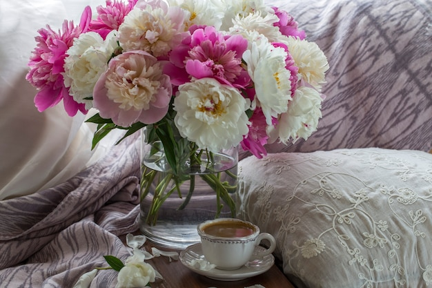 On the table is a cup of coffee and a bouquet of peonies