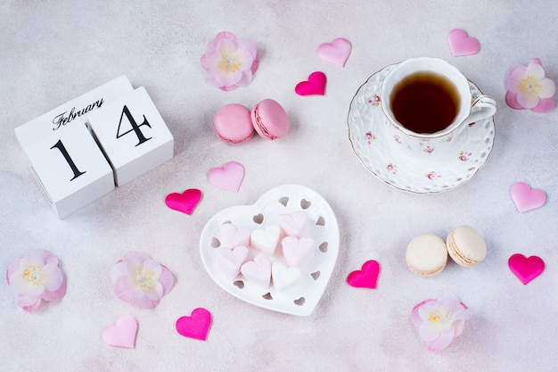 On the table is a cup of tea, pink flowers, heart-shaped marshmallows, satin hearts, macaroons and a calendar date of february 14