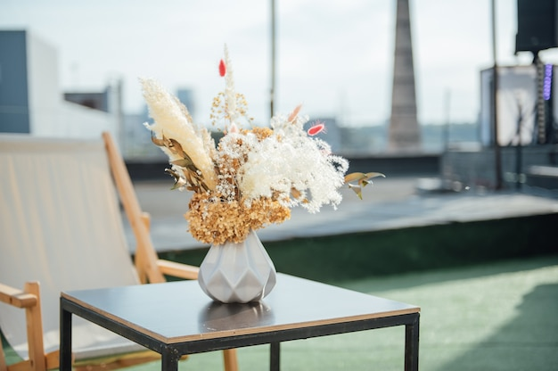 On the table is a decorative vase with dried flowers. beautiful summer location for relaxation on a roof
