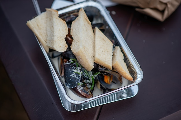 On the table is a disposable foil plate containing fire-baked mussels in garlic sauce, sprinkled with parmesan cheese and a crispy fresh baguette. street takeout fast food at the festival. copy space
