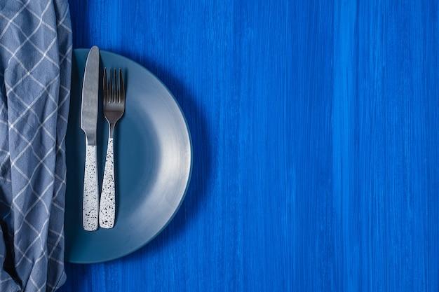 青い背景の上のテーブルナイフとフォーク。