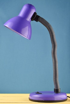 Table lamp on a table isolated against a blue wall background