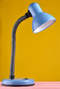 Table lamp on a table isolated against a yellow wall background