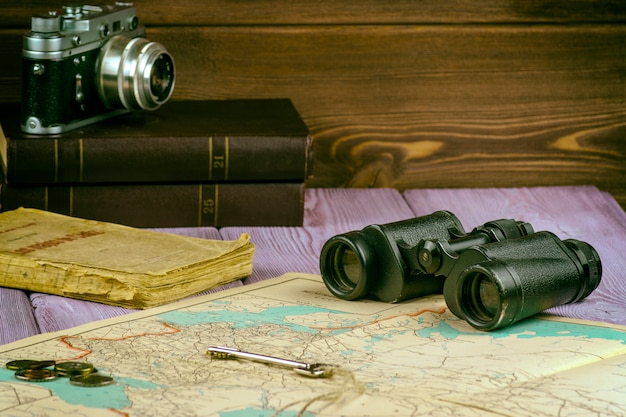 On the table lay an old book, map, coins, a key and a pair of binoculars and there is a film camera.