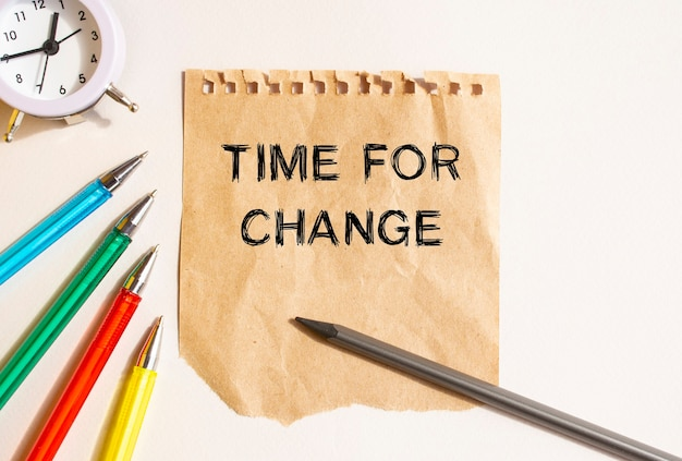 On the table lies a rumpled sheet of kraft paper torn from a notebook. text on the time for change sheet. colored pens, clock and pencil. concept for your design.