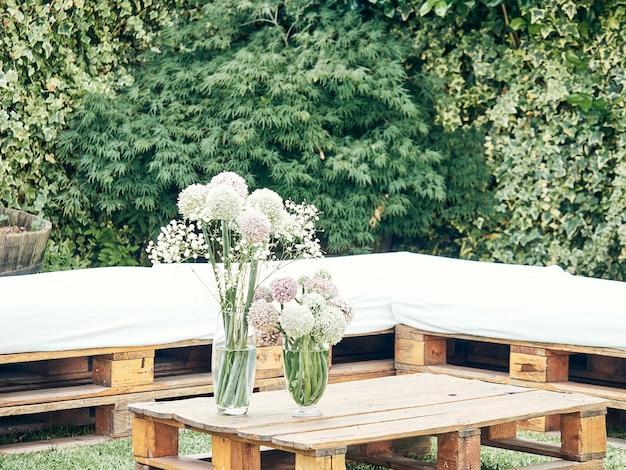 Стол из деревянных поддонов, украшенный вазой с цветами, концепция свадебного украшения
