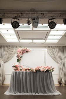 The table for the newlyweds is decorated with fresh flowers in the restaurant. square lighting and spotlights