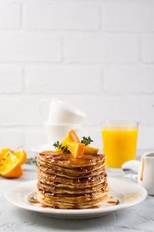朝食のテーブル。オレンジとメープルシロップ、オレンジジュース、コーヒーをまぶしたパンケーキ