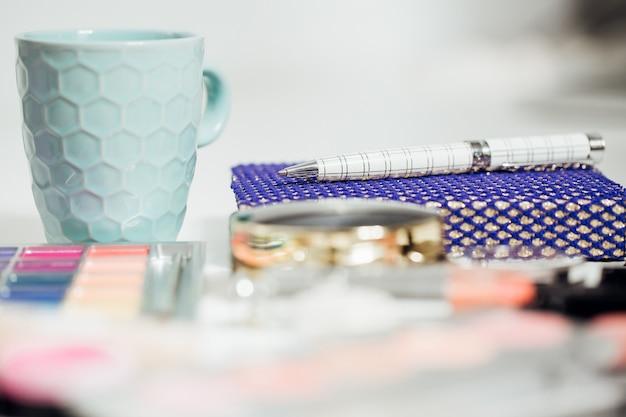 女性のテーブル。ノート、ペン、コーヒーカップ