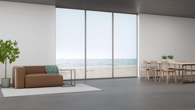 モダンなビーチハウスまたは高級ホテルのリビングエリアとソファの近くの広いダイニングルームのコンクリートの床にあるテーブル。