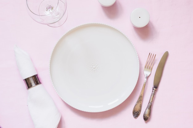 Table place setting on pink linen tablecloth. top view.