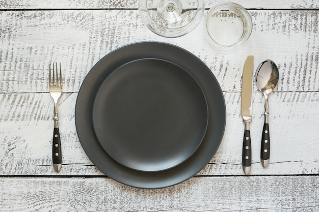 Table place setting with black plate on white wooden table. top view.