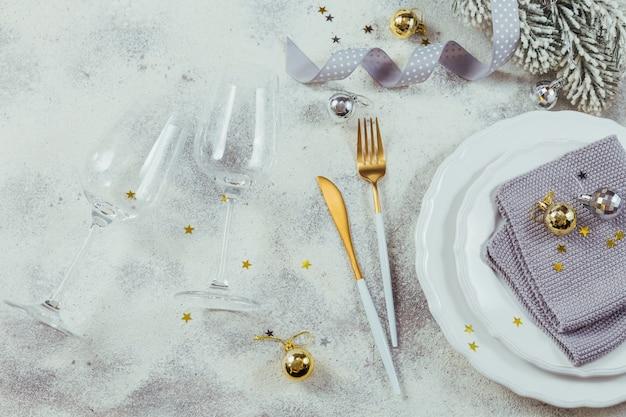 休日の装飾が施されたテーブルの場所の設定。カトラリー、クリスマスプレゼント、モミの枝、白い背景の上の装飾。ロマンチックなディナーのコンセプト。フラットレイ、上面図、コピースペース。