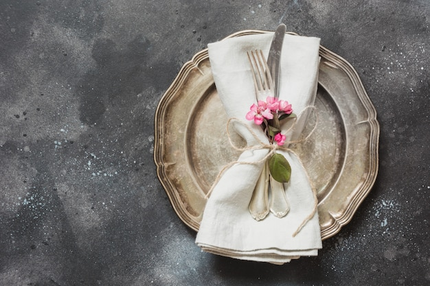 Table place setting with pink flowers, silverware on vintage background.