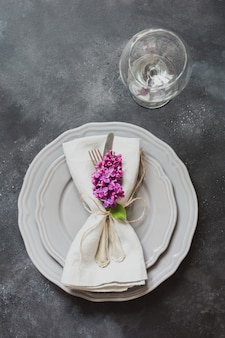 Table place setting with pink lilac flowers, silverware on vintage background.