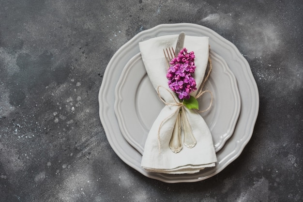 Table place setting with purple lilac flowers, silverware on vintage background.