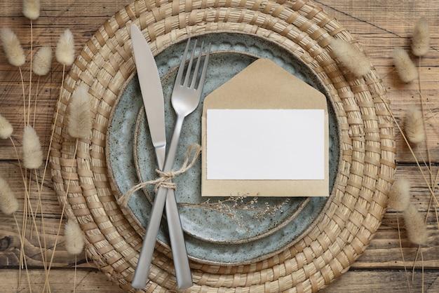 Столовое место с пустой бумажной карточкой, вилкой, конвертом и ножом на тарелках в окружении засушенных цветов