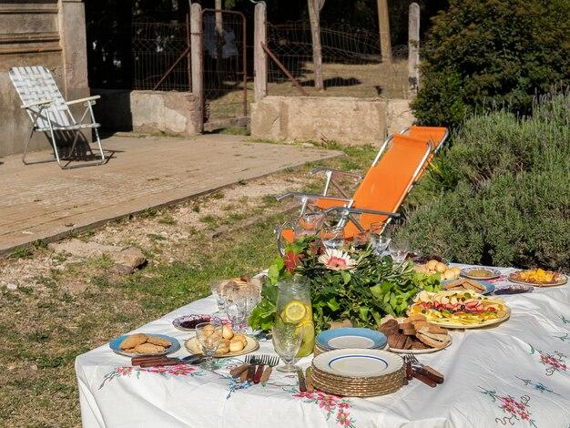パンや果物などの食べ物が入った花で飾られた、庭での会議用に用意されたテーブル。アンティークガラス製品。