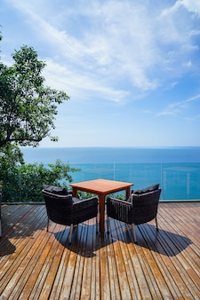 Table and rattan outdoor armchair on wooden deck and glass balcony