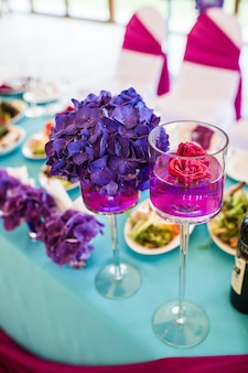 Table in the restaurant decorated with purple flowers, wedding dinner