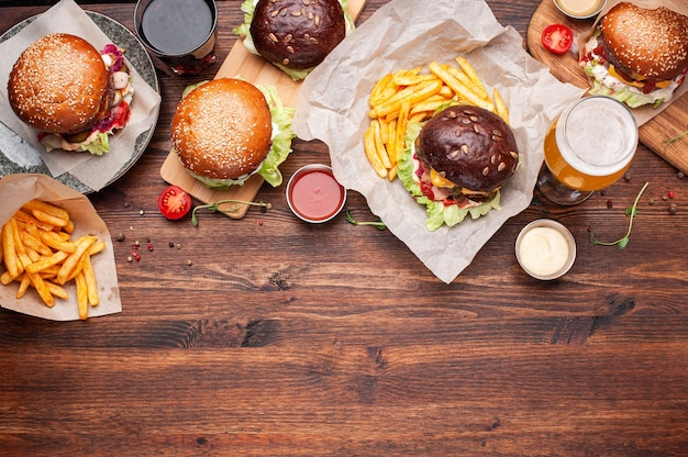 Table scene of burgers, french fries, drinks, sauces and vegetables. horizontal shot with space for text.