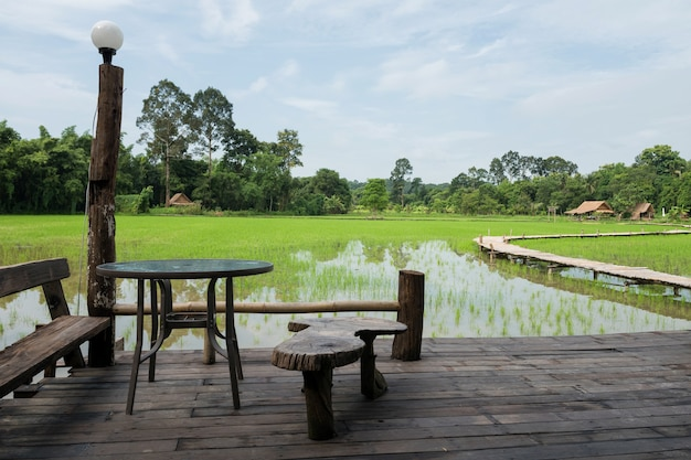 Table and seats on wood balcony to see paddy rice field farm with curve wooden footpath and farmer hut, nakhon nayok, thailand. famous scenic travel landmark or holiday maker in .