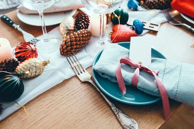 リビングルームでのクリスマスディナーのテーブル。ビュー、テーブルの設定、プレート、ブランチ装飾、キャンドル、木製のテーブル背景にきらめくおもちゃを閉じます。冬の装飾