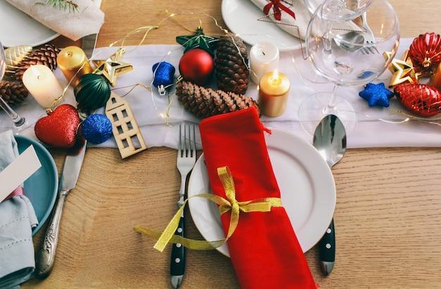 リビングルームでのクリスマスディナーのテーブル。クローズアップビュー、テーブルの設定、プレート、ブランチの装飾、キャンドル、木製のテーブル背景に輝くおもちゃ