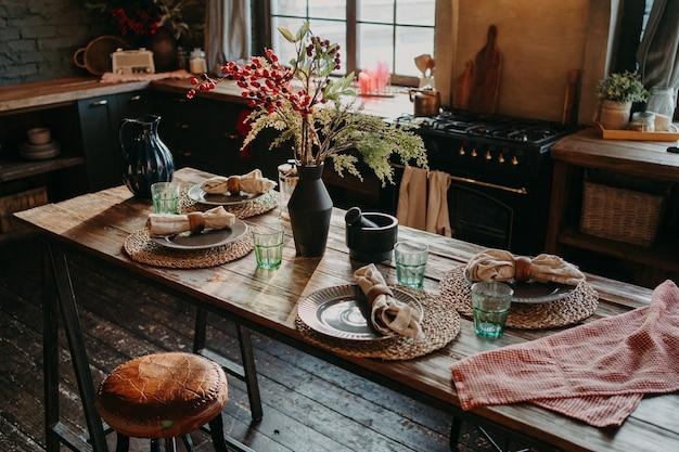 夕食にはテーブルを用意。居心地の良いキッチンインテリア。ゲスト用のテーブルの上のカトラリーとナプキン。家族の朝食。食事の時間。無人。